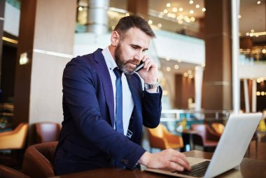 Businessman working in hotel calling to his partner
