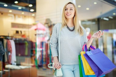 Blond girl with shopping bags shopping in trade center stock vector