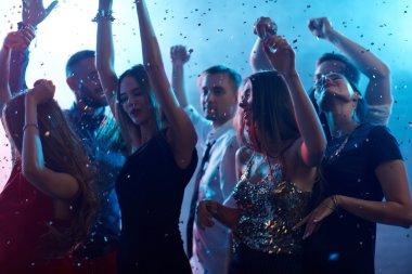 Ecstatic people dancing in night club