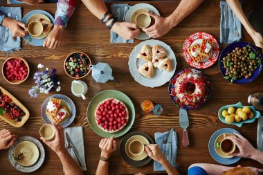 Hands of friends over served festive table