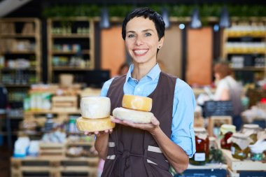 Seller of dairy products holding cheese