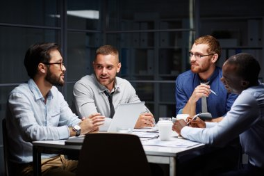 Businessmen having late discussion in office