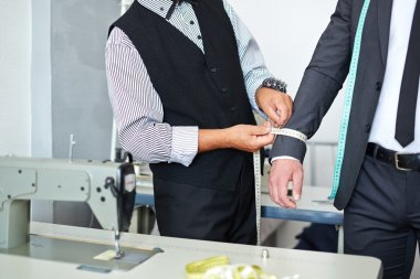 Tailor measuring girth of jacket sleeve