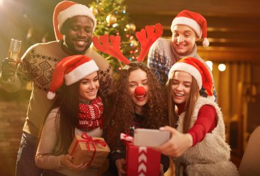 Happy friends making Christmas selfie