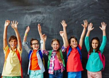 Schoolkids raising hands at chalkboard