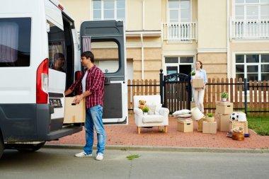 Man putting carton box into van