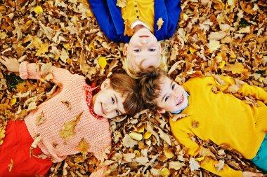 Three Kids Lying in Fallen Leaves