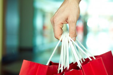 male hand holding shopping bags