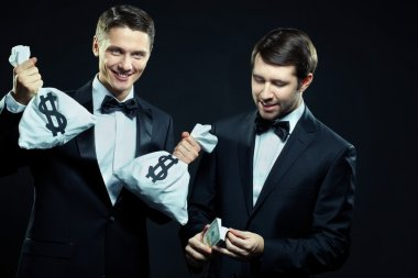 Two smiling men counting dollars