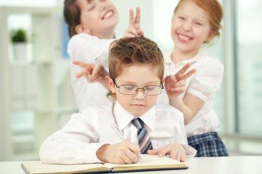 Girls teasing a boy making classwork
