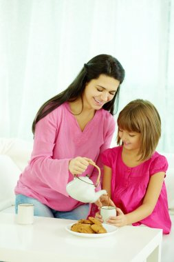 Mother pouring tea into daughter's cup