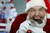 Wicked Santa Claus devouring chocolate