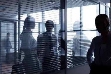 business people communicating behind glass wall