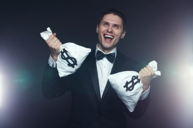 Mad businessman with two money bags