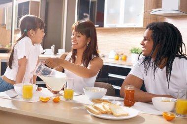 Happy family having breakfast at the table
