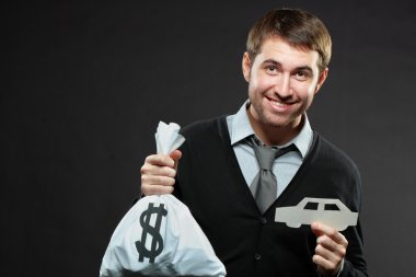 man holding money bag and paper car