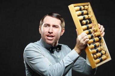 Aggravated businessman holding an abacus