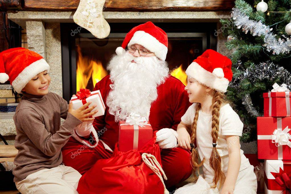 an image of santa claus sitting at fireplace and christmas tree and giving presents to two children photo by pressmaster - Santa Claus With Presents