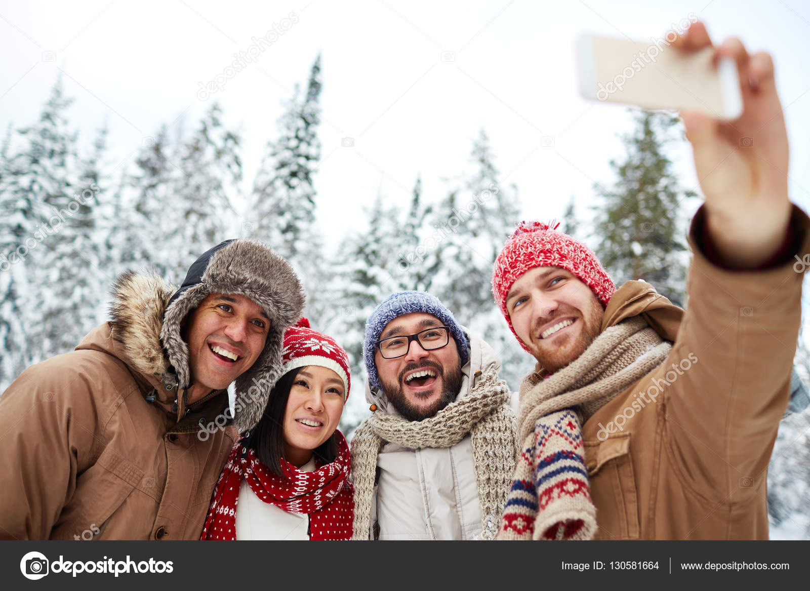 Men and woman taking selfie in winter forest — Stock Photo