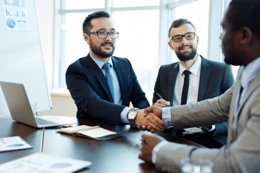 Business partners handshaking after signing contract