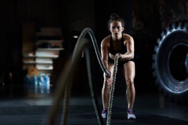 Young woman doing battle rope exercises