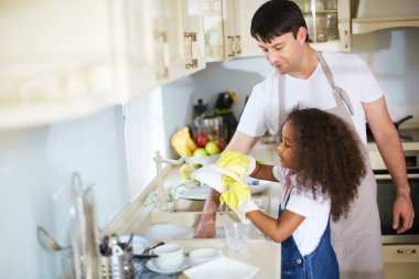 girl washing dishes with father