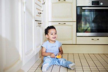 kid sitting on kitchen floor