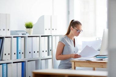 accountant looking through papers at workplace