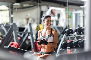 Smiling woman listening to music in gym