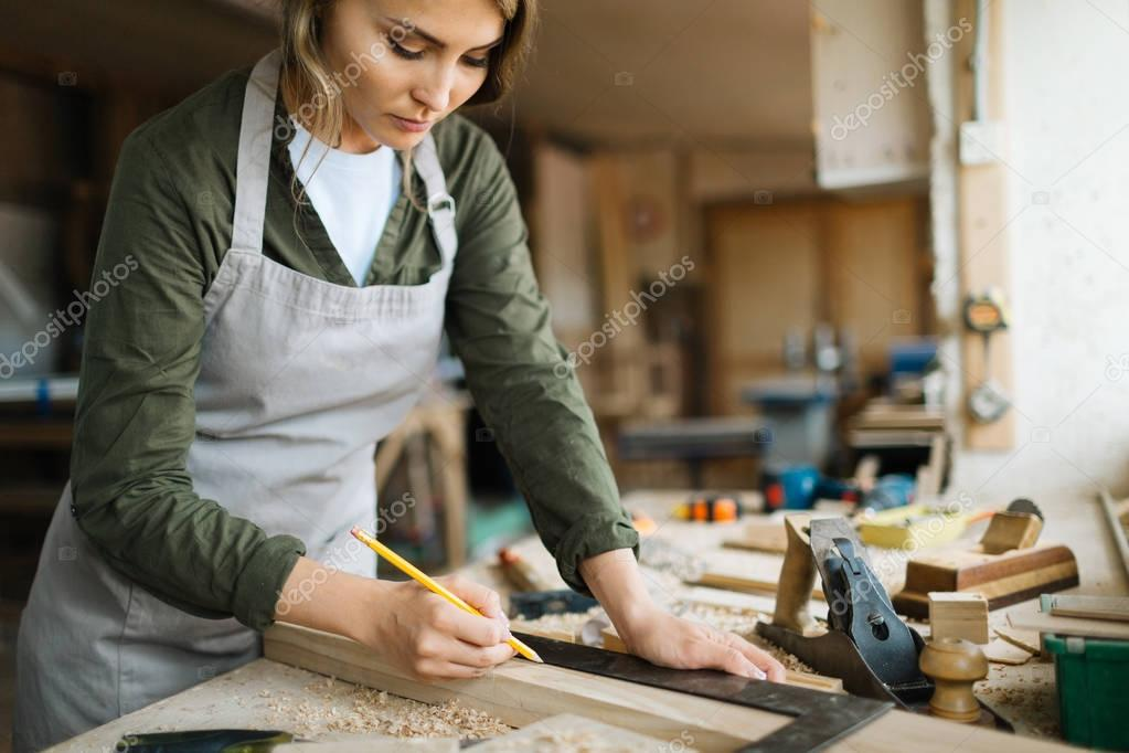 Young carpenter measuring plank