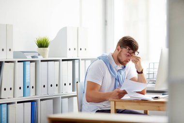 Tired businessman sitting by workplace