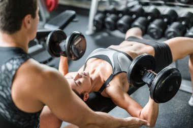 Woman with dumbbells exercising with trainer