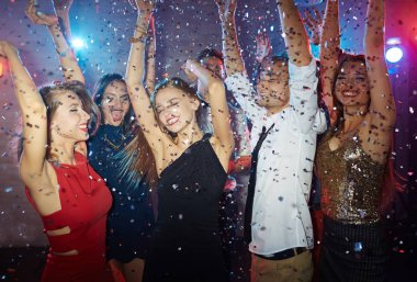 friends dancing with raised hands at disco
