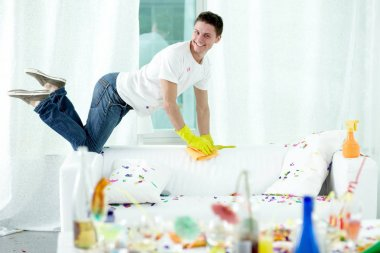 man putting room in order after party