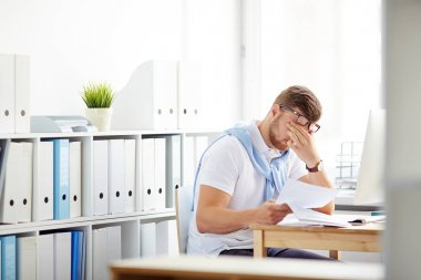 Tired accountant sitting at workplace