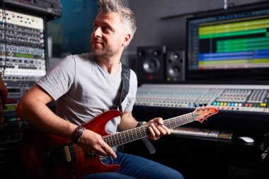 musician playing the guitar in recording studio