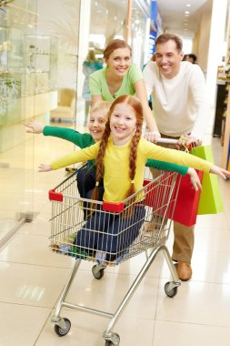 parents carrying their children in shopping cart