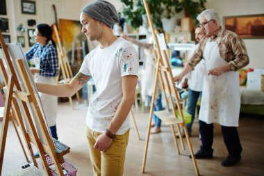 young artists painting on easel