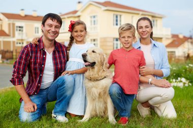 Happy family with dog looking at camera