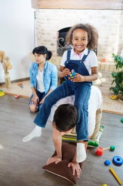 Girl playing with father in living-room