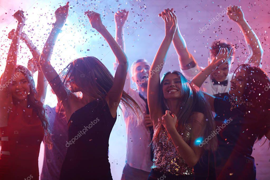Ecstatic friends dancing in confetti rain