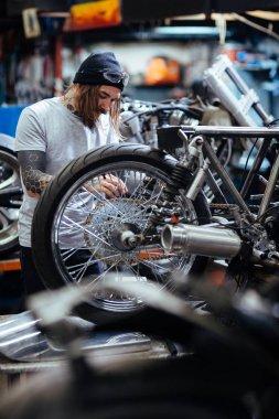 Hipster repairing custom-bike in workshop