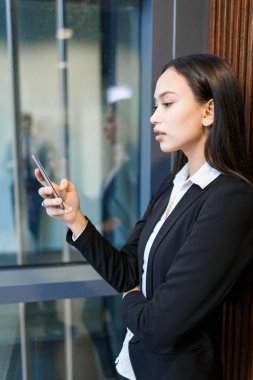 Young businesswoman reading sms