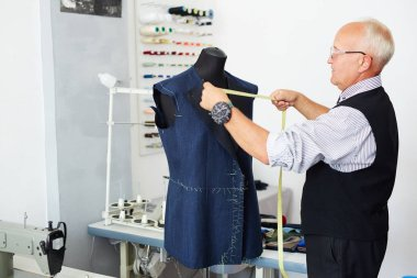 Senior tailor working with mannequin