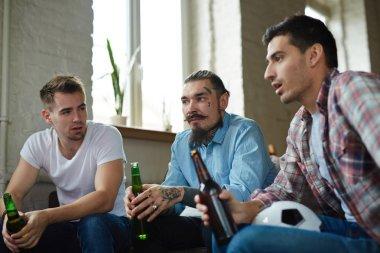Tense guys watching tv broadcast