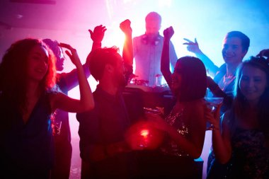couple with friends dancing at night party