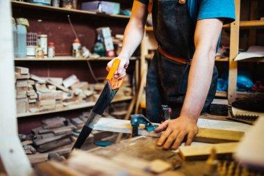 Handyman sawing plank