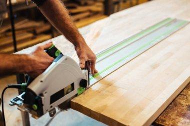Workman processing wooden board in workroom