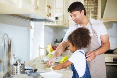 Little girl washing dishes