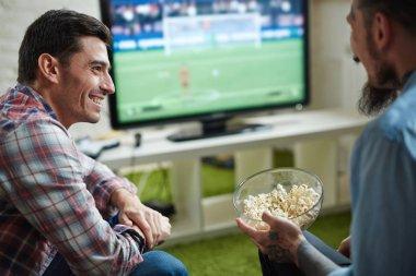 Friends watching football broadcast